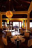 MAURITIUS, Chemin Grenier, two men talk on the balcony in front of the main restaurant Pebbles, Hotel Shanti Maurice