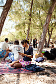 MAURITIUS, friends are enjoy some shade and a picnic on the beach at Ile Aux Cerfs Island