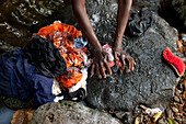 MAURITIUS, Bois Cherie, Mutty Megah (age 63) washes her clothes in a small stream behind her home