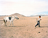 MONGOLIA, Khuvsgul National Park, a young boy attempts to lead his horse in a wide open landscape