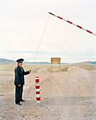 MONGOLIA, Khuvsgul National Park, a man operates the entry gate into Khuvsgul National Park