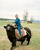 MONGOLIA, Batkhuu's home near Khuvsgul Lake, portrait of a smiling boy riding a yak, Khuvsgul National Park