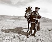 MONGOLIA, shehperd Batsuuriin stands with his horse Khaltar and watches his lifestock, the Gobi Desert, Nemegt Basin (B&W)