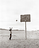 MONGOLIA, Khuvsgul National Park, a young boy shoots a basketball in a wide open barren landscape (B&W)