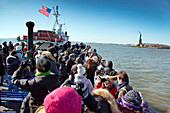 USA, New York, tourists on a boat tour to visit the Statue of Liberty National Monument and Ellis Island