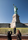 USA, New York, a woman having her photo taken in front of the Statue of Liberty