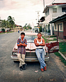 PANAMA, PANAMA, Bocas del Toro, young men rest against their car on Main Street, Central America