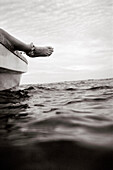 PANAMA, Bocas del Toro, a woman relaxes and hangs her foot off the side of a boat, Central America (B&W)