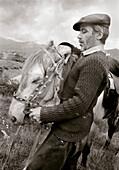 REPUBLIC OF GEORGIA, mid adult man bridling a horse (B&W)