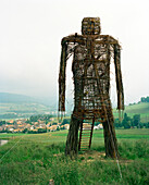 SWITZERLAND, Motiers, a sculpture of a figure made of wood and branches adorns the hillside above town, Jura Region