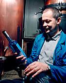 SWITZERLAND, Couvet, Absinthe maker Claude-Alain Bugnon holding a bottle at his Artemisia Distillerie, Jura Region