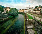 SWITZERLAND, Couvet, L'arerse River running through the center of town, Jura Region
