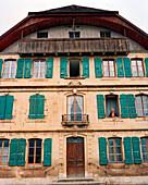SWITZERLAND, Bouvresse, an elderly woman Jaquline Petit-Pierre looks out the window of an old pensione, Jura Region