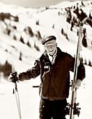 USA, Utah, portrait of a senior man holding skis and ski poles, 80+ ski club, Alta Ski Resort (B&W)