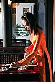 VIETNAM, Hue, Ms. Boi Tran's Hoang Vien restaurant, a woman in traditional dress pours tea