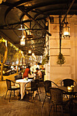 VIETNAM, Hanoi, Sofitel Metropole Hotel, a server brings dinner to a guest at an outdoor table