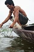 VIETNAM, Hue, Perfume river, fisherman Tran Van Son with his casting net in his Sampan boat, La Y Village, Phu Vang District, Thua Thien Hue Province