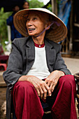 VIETNAM, Hue, an elderly woman sells peanuts outside in front of an old monastery