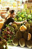VIETNAM, Saigon, Ben Thanh Market, a vendor arranges the Duran or Kho Qua Xanh, one is split open showing the fruit inside, Ho Chi Minh City