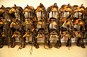 USA, Wyoming, Encampment, horse saddles hanging on a wall in a tack room, Abara Ranch