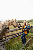 USA, Wyoming, Encampment, a woman and her son pet a horse on the nose, Abara Ranch