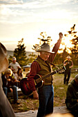 USA, Wyoming, Encampment, A guitar player raises his arm after finishing his final song by the campfire