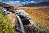 Blick über den Abisko Nationalpark mit Wasserfall im Vordergrund und Lapporten im Hintergrund im Herbst, Lappland, Schweden