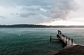 Two young men standing on a jetty at Lake Starnberg in rain, Bavaria, Germany