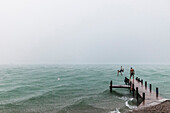 Two young men on a jetty at Lake Starnberg in rain, Bavaria, Germany