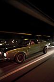 Man driving a modern classic car at night, Motoraver group, Hamburg, Germany
