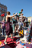 Musician playing music on top of a power box, woman hula hooping at her stand, fleamarket at Schanzenfest, Schanze district, Hamburg, Germany