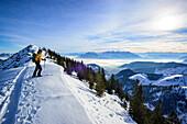 Female back-country skier ascending to Grosser Traithen, Kaiser mountain range in background, Mangfall range, Bavarian Alps, Upper Bavaria, Bavaria, Germany