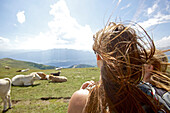 Two young women looking at a herd of cows, Alpe-Adria-Trail, Nockberge, Carinthia, Austria