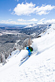 Man downhill skiing in deep snow, Mammoth Mountains, California, USA