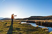 Flying fisherman at Hot Creek in sunset, Mammoth Lakes, California, USA