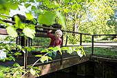 Boy (2 years) on a weir, near Boitzenburg, Uckermark, Brandenburg, Germany