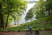 Cyclist passing lake Schmaler Luzin, Feldberger Seenlandschaft, Mecklenburg-Western Pomerania, Germany