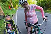 Female cyclist lookint to son in a child transporter, Feldberger Seenlandschaft, Mecklenburg-Western Pomerania, Germany