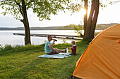 Father and son having dinner near a tent at lakeside, Lychen, Uckermark Lakes Nature Park, Uckermark, Brandenburg, Germany