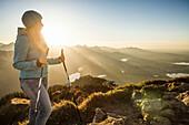 Hiker standing on rocky hilltop. Branderschrofen, Tegelberg