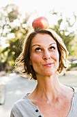 Woman balancing apple on head outdoors
