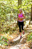 A 38 year old blond woman wearing work-out clothing jogging on a trail in a forest setting in the fall