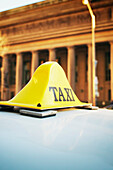Taxi Sign on Roof of Car