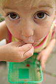 Close Up of a Little Girl Eating a Raspberry, Toronto, Ontario