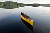Yellow canoe floating on Smoke Lake, Algonquin Park, Ontario
