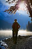 Woman hiking on misty fall morning, Maligne Lake, Jasper National Park, Alberta