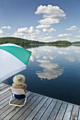Woman sitting under umbrella on dock, Smoke Lake, Algonquin Park, Ontario