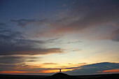 Man with arms outstretched on top of butte, at sunset, Grasslands National Park, Saskatchewan