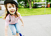 Smiling blond girl with helmet standing on bike, Otterburn Park, Quebec