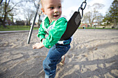 Toddler playing on swing in park, Toronto, Ontario